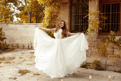 Beautiful bride woman in blowing wedding dress out Royalty Free Stock Photography