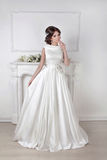 Beautiful bride woman posing in magnificent dress over white wal Stock Photos