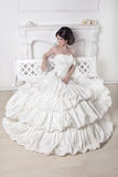 Beautiful bride woman sitting on luxuriant wedding dress over wh Stock Photography