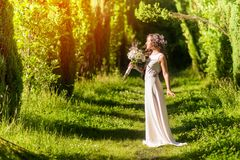 Beautiful bride. With wreath outdoors holding wedding bouquet royalty free stock photos