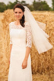 Beautiful bride on yellow field near haystack Royalty Free Stock Photos
