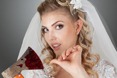 Beautiful bride. Beautiful young bride with bloody ax in hands studio indoor portrait Royalty Free Stock Photography