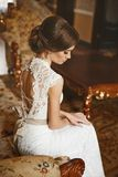 Beautiful bride, young model brunette woman, in stylish wedding dress with naked back sits on the vintage sofa and posing in luxur stock image