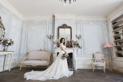 Beautiful bride, young model brunette woman, in stylish wedding dress with naked shoulders, with bouquet of flowers in. Her hands, posing in luxury vintage Stock Photos
