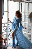 Beautiful bride young woman in a blue long peignoir in a wedding morning. Fashion beauty portrait Royalty Free Stock Photos