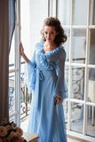 Beautiful bride young woman in a blue long peignoir in a wedding morning. Fashion beauty portrait Stock Images