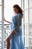 Beautiful bride young woman in a blue long peignoir in a wedding morning. Fashion beauty portrait Stock Image