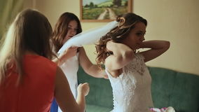 Beautiful bridesmaids helping the happy bride getting dressed. Beautiful bridesmaids helping the happy bride getting dressed stock footage
