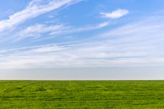 Beautiful bright blue sky and lush green grass as a background or backdrop.  stock photo