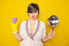 Beautiful bright brunette in a Bathrobe holds a pan and a sponge for washing dishes. young woman housewife on yellow studio backgr royalty free stock image