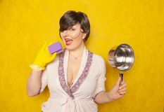 Beautiful bright brunette in a Bathrobe holds a pan and a sponge for washing dishes. young woman housewife on yellow studio backgr royalty free stock photo