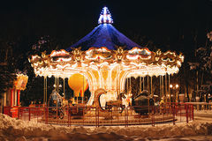 Beautiful bright carousel in park at night in winter Stock Image
