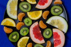 Beautiful bright citrus fruit cut into pieces slices in a large plate black on light blue fabric background kitchen towel close-up royalty free stock image
