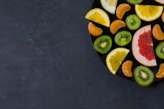 Beautiful bright citrus fruit cut into pieces slices in a large plate black stone grey dark black background with copyspace stock image