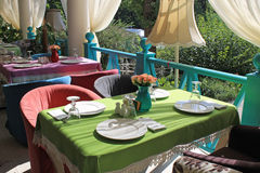 Beautiful bright colored terrace in country restaurant. Beautiful terrace with bright colored armchairs and tableclothes in country restaurant Royalty Free Stock Photos