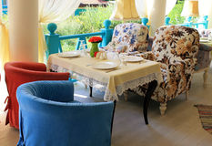 Beautiful bright colored terrace in country restaurant. Beautiful terrace with bright colored armchairs and tableclothes in country restaurant Royalty Free Stock Images