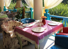 Beautiful bright colored terrace in country restaurant. Beautiful terrace with bright colored armchairs and tableclothes in country restaurant Stock Photography