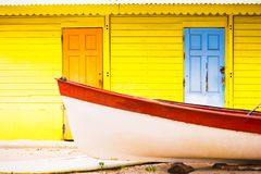 Beautiful bright colored wooden house on sea side with colorful wooden boat in front royalty free stock photography