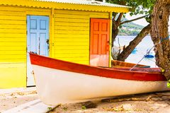 Beautiful bright colored wooden house on sea side with colorful wooden boat in front stock images