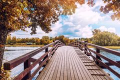 Beautiful bright colorful autumn landscape, a wooden bridge across the lake river in the forest royalty free stock images