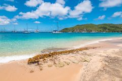 Princess Margaret beach, Bequia Island, Saint Vincent and the Grenadines. Beautiful bright and colorful image with turquoise sea and white sand beach. Ships and royalty free stock photo