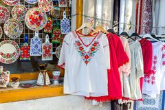 Ethnic shirts with traditional Hungarian embroidery and decorative painted plates and cutting boards in a street store. Beautiful bright ethnic shirts with Royalty Free Stock Image