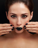 Beautiful bright evening makeup woman, black nails polish and black lipstick. Looking serious on black background Stock Photo