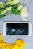 Flowers are spread around a mobile phone with a broken screen. Beautiful bright flowers are spread around a modern mobile phone with a broken screen. View from stock image