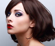 Beautiful bright makeup with blue eyeshadows. Short hair style. Beautiful bright makeup with blue eyeshadows and red lipstick. Short hair style. Closeup Stock Image