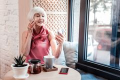 Beautiful bright old woman correcting her accurate hairstyle. Small pocket mirror. Beautiful bright old woman correcting her accurate hairstyle while inspecting royalty free stock image