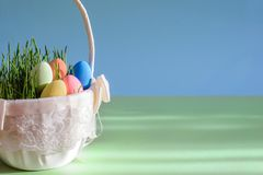 Beautiful bright picture with Easter eggs in basket on blue-green background with copy space Stock Photography