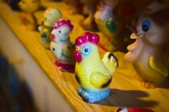 Beautiful bright plastic toy rooster on wooden royalty free stock photography