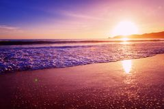 Beautiful bright purple purple sunset on the ocean, sandy beach, waves and glare of the sun royalty free stock image