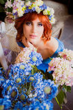 Beautiful bright red haired girl with flowers. Photo taken 08.22.2015 Stock Photo