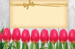 Beautiful bright tulips and card with golden bow on wooden Stock Photography
