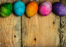 Happy Colors - beautiful, bright, very colorful hand-painted Easter eggs on a contrasting, raw, natural background from wooden pla royalty free stock photography