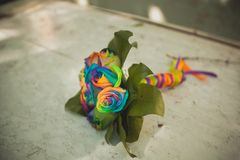 Beautiful bright wedding bouquet on an old shabby wooden table, close-up. The bride`s bouquet of colorful roses, tied with a sati stock image