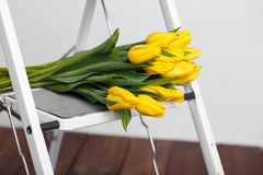 Beautiful bright yellow tulips More lying on sofa white stairs Royalty Free Stock Photos
