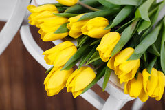 Beautiful bright yellow tulips in Still Life lying on antique white Chair Stock Photos