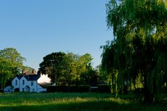 Beautiful British country house. Surrounded by trees, grass, and blue clear sky in the background Stock Photos