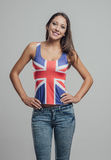 Beautiful British girl posing. Beautiful confident girl posing with arms akimbo and wearing a British flag tank top, she is smiling at camera Royalty Free Stock Photography