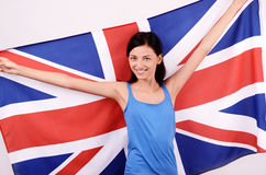 Beautiful British girl smiling holding up the UK flag. Royalty Free Stock Photography