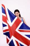 Beautiful British girl smiling holding up the UK flag. Stock Image