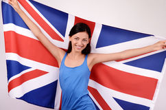 Beautiful British girl smiling holding up the UK flag. Stock Photos