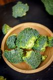 Beautiful broccoli florets on a wooden plate on a slate board. Beautiful broccoli florets on a wooden plate on a slate board Royalty Free Stock Photos