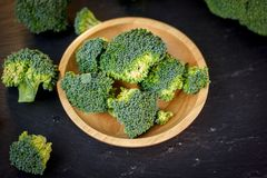 Beautiful broccoli florets on a wooden plate on a slate board. Beautiful broccoli florets on a wooden plate on a slate board royalty free stock photography