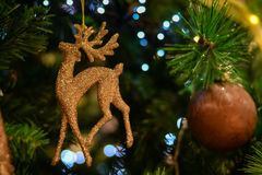 Beautiful bronze deer glittered ornament on. Picture of beautiful bronze deer glittered ornament. Closeup of charming decor on christmas tree with bokeh on Royalty Free Stock Photo