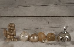 Beautiful bronze and golden glass christmas baubles and candle and angel, on sheepskin Stock Image