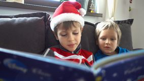 Beautiful brothers reading a story, Christmas day. Hd video stock footage