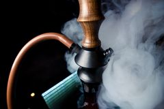 A black hookah stands on a glass table stock photo